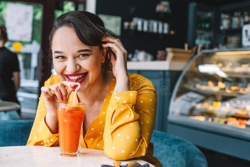 Happy beautiful plus size woman smiling and drinking healthy carrot smoothie in cafe royalty free stock images