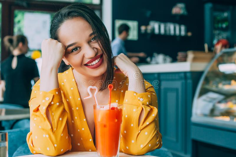 Happy beautiful plus size woman smiling and drinking healthy carrot smoothie in cafe stock photography