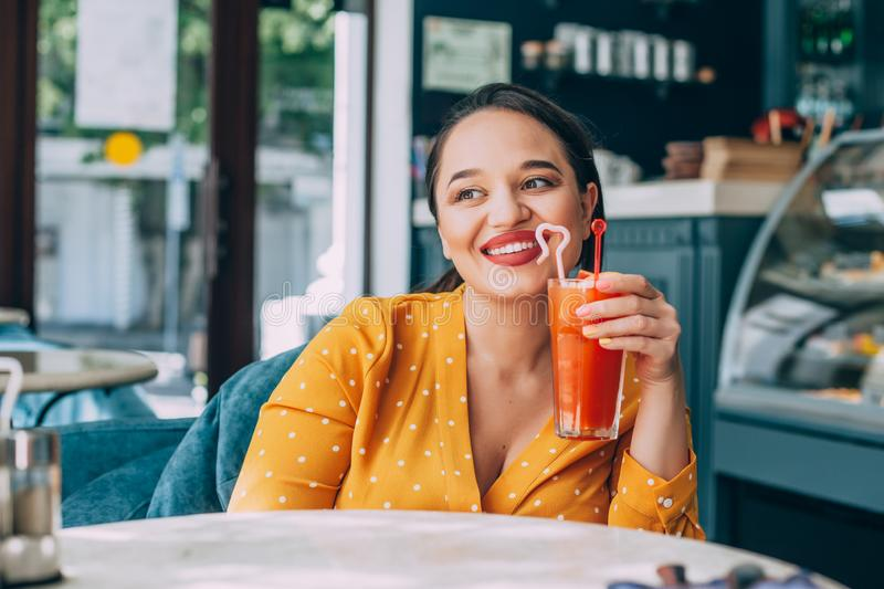 Happy beautiful plus size woman smiling and drinking healthy carrot smoothie in cafe stock images