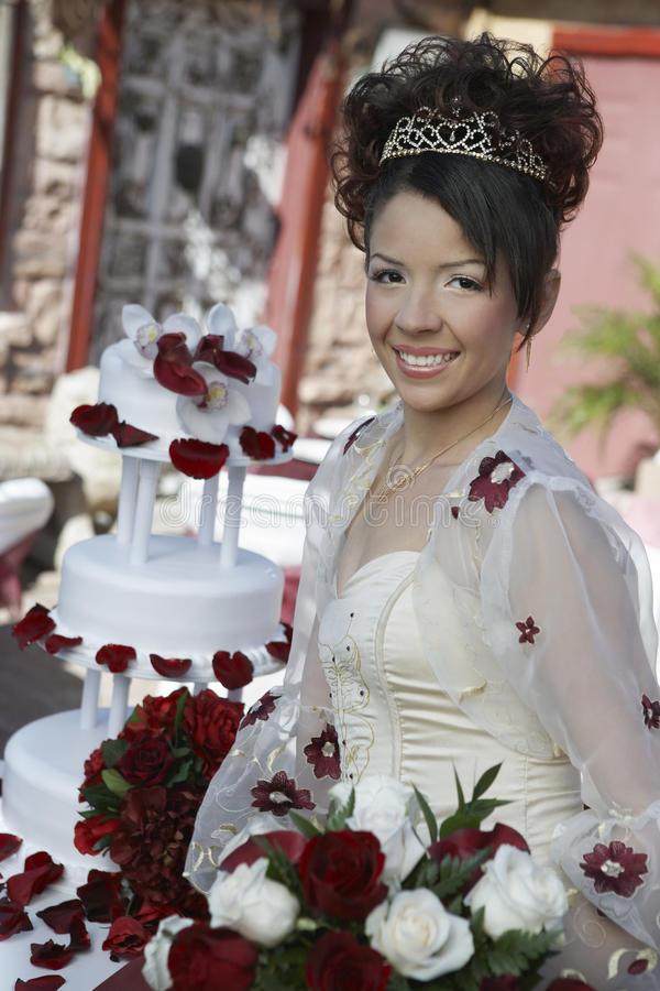 Happy Beautiful Quinceanera Holding Flowers. Portrait of a happy beautiful Quinceanera holding flowers with wedding cake in background stock photography