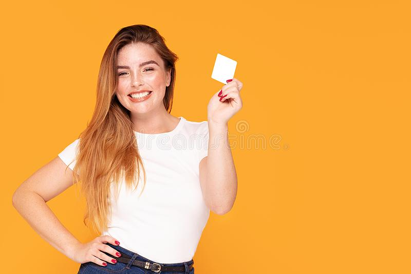 Smiling student girl holding credit card. Happy beautiful redhead woman holding credit card in hand, smiling, posing in studio royalty free stock images
