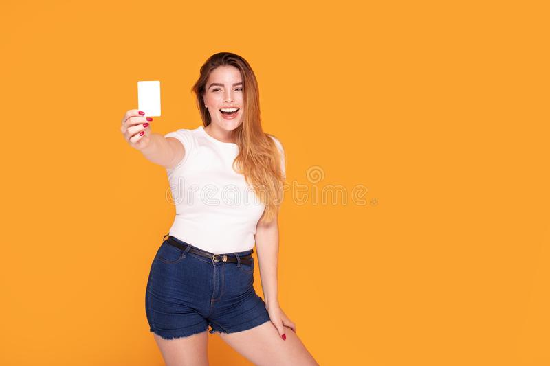 Smiling student girl holding credit card. Happy beautiful redhead woman holding credit card in hand, smiling, posing in studio stock photos