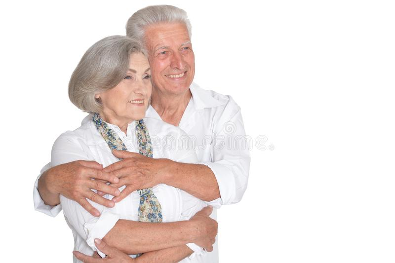 Happy beautiful senior couple huging and posing on white background royalty free stock images