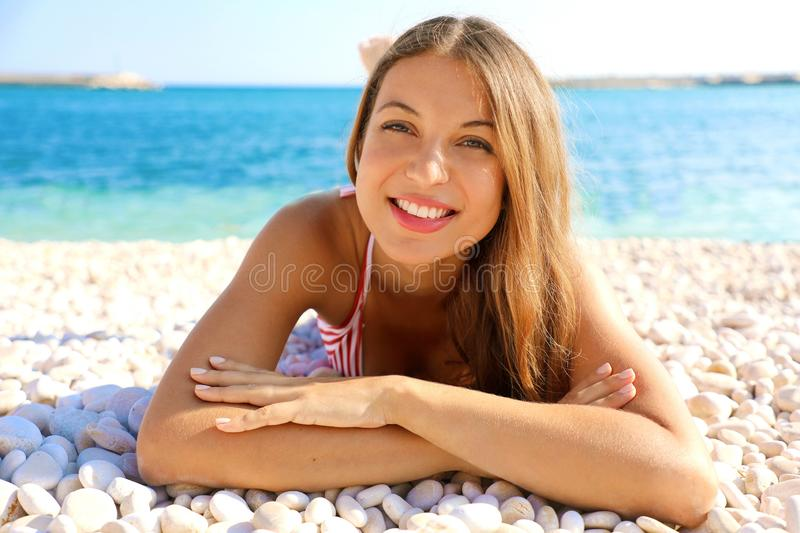 Happy beautiful smiling girl enjoying relax lying on the beach looking at camera. Summer holidays concept stock images