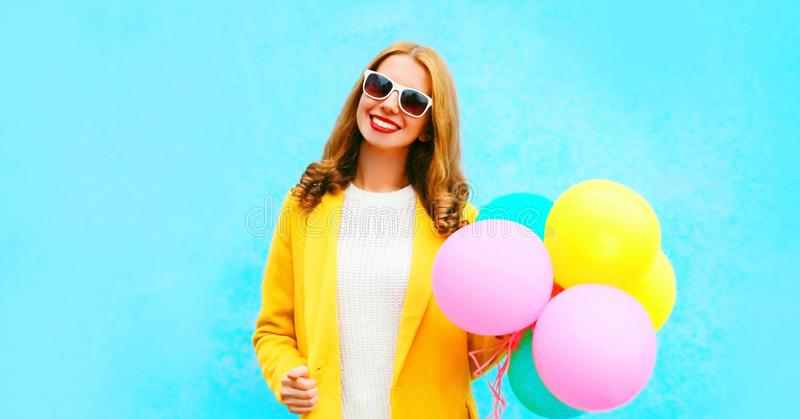 Happy beautiful smiling woman holds an air balloons in yellow coat royalty free stock photo