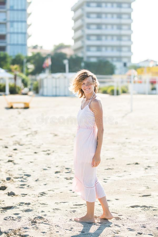 Happy beautiful smiling young woman walk at the sand beach, looking at camera stock image