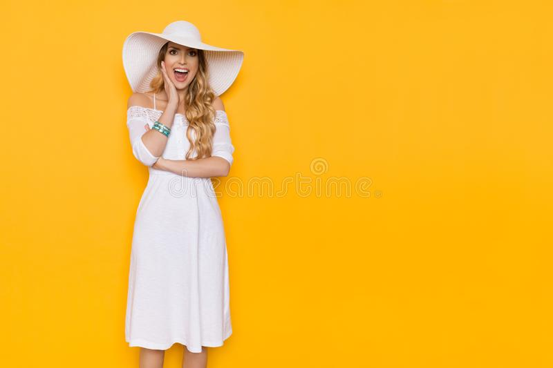 Happy Beautiful Smiling Young Woman In White Dress And Sun Hat Is Shouting. Beautiful young woman in white summer dress and sun hat is holding hand on chin stock photography