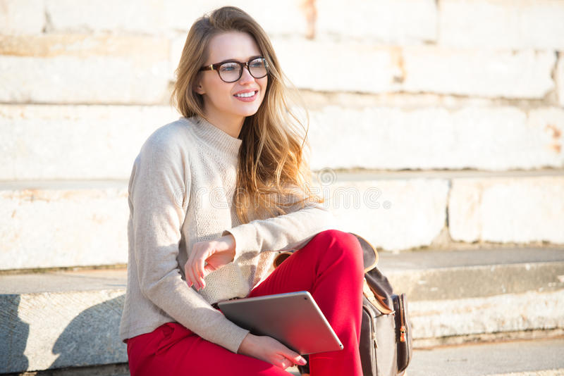Happy beautiful student girl wearing eyeglasses sitting on college steps in the campus with a bag and tablet stock photos