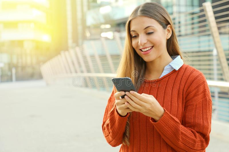 Happy beautiful student woman writing or reading sms messages online on a smart phone while standing in modern city street. Copy stock image
