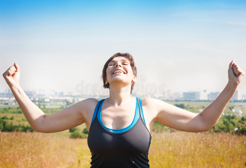 Happy beautiful successful plus size woman raising arms to the s stock photos
