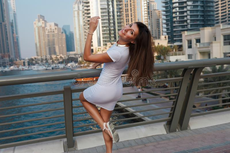 Happy beautiful tourist woman in fashionable summer white dress walking and enjoying in Dubai marina in United Arab Emirates. Luxury and comfortable tourism royalty free stock photography