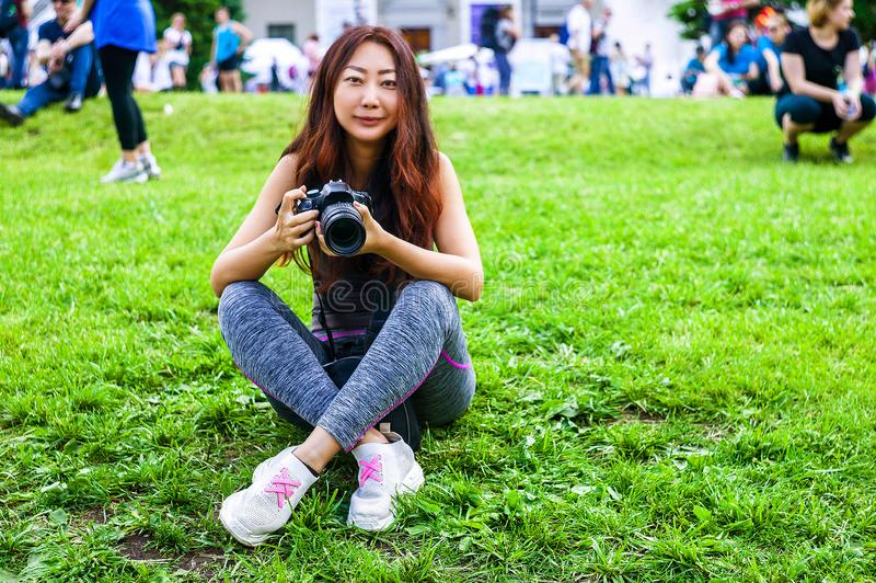 Happy beautiful traveler asian woman with camera. Young joyful asian women using camera to making photo during city tour. royalty free stock photography
