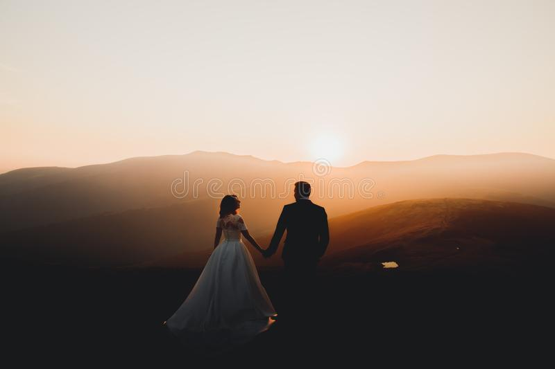 Happy beautiful wedding couple bride and groom at wedding day outdoors on the mountains rock. Happy marriage couple. Outdoors on nature, soft sunny lights stock photography
