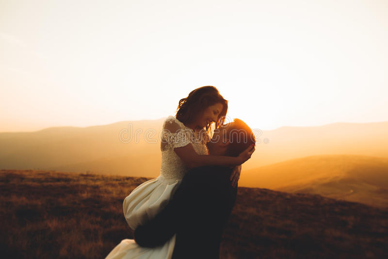Happy beautiful wedding couple bride and groom at wedding day outdoors on the mountains rock. Happy marriage couple. Outdoors on nature, soft sunny lights royalty free stock photo