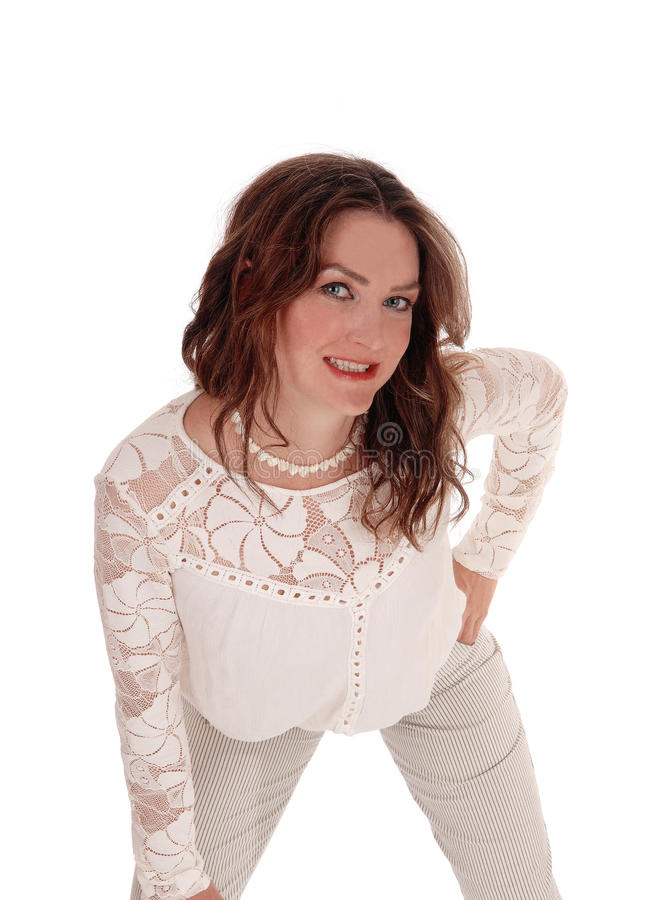 Happy beautiful woman bending forwards. A slim young gorgeous woman standing in dress pants and a lace blouse bending forwards, smiling, isolated for white stock photo