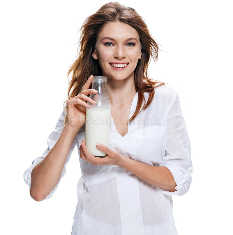 Happy beautiful woman with bottle of milk isolated on white. Jolly girl of the european appearance in a white shirt holds a bottle of milk - isolated on white royalty free stock photo