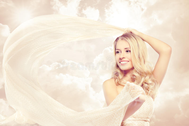 Happy beautiful woman carefree dancing with flying fabric. Happy woman, beautiful blonde carefree dancing with flying fabric over sunshine sky royalty free stock photography
