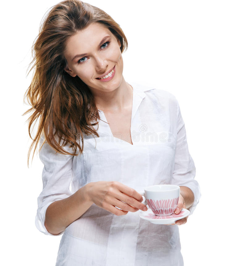 Happy beautiful woman with coffee cup in hands isolated on white. Relaxed european-looking girl in a white shirt with cup and saucer - on a white backgroundrn stock photo