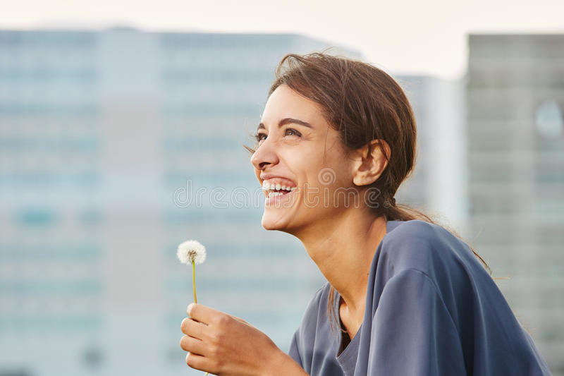 Happy beautiful woman with dandelion. Close up side portrait of happy beautiful woman holding dandelion and laughing royalty free stock photography