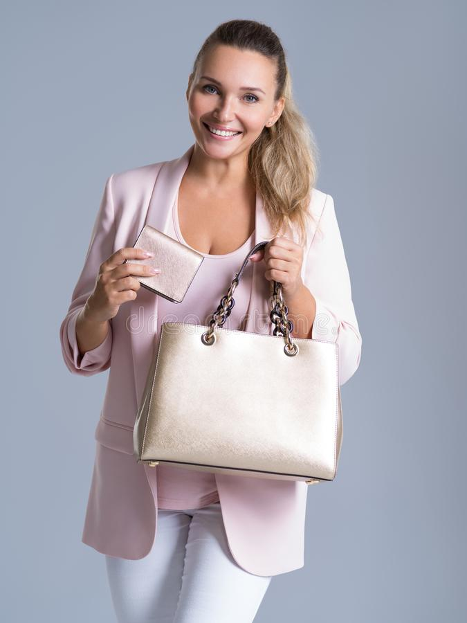 Happy beautiful woman with handbag and wallet in shopping royalty free stock photography