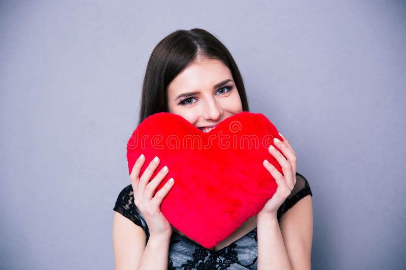 Happy beautiful woman holding red heart. Over gray background and looking at camera stock photo
