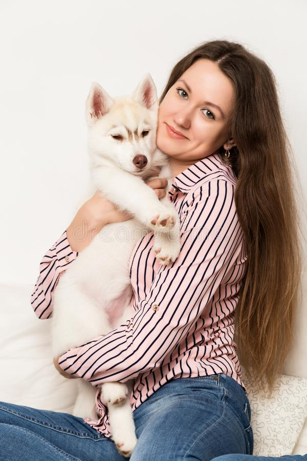 Happy beautiful woman hugging puppy husky. girl sitting on a sofa with a dog.  stock photography