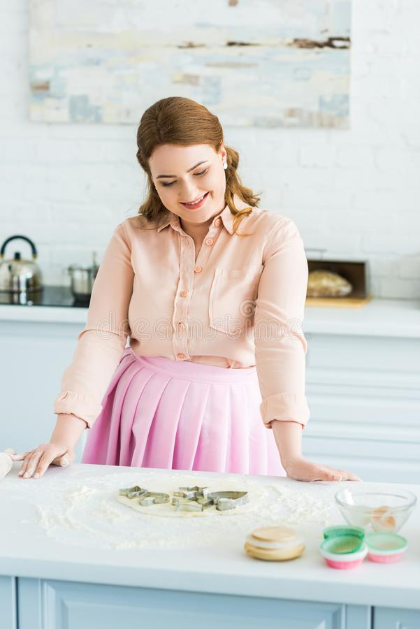 happy beautiful woman looking at baking molds royalty free stock photography