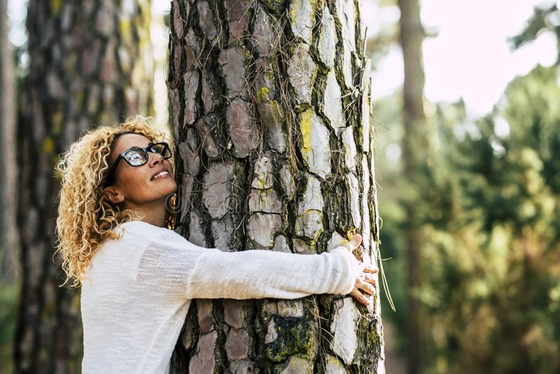 Happy beautiful woman love nature hugging a pine tree - no deforestation concept and earth`s day celebration - save our planet fo royalty free stock photography
