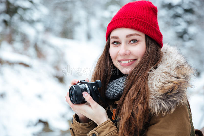 Happy beautiful woman photograher taking photos in winter forest stock images