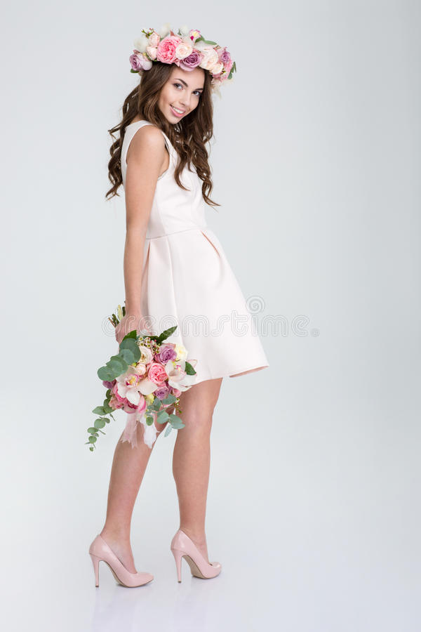 Happy beautiful woman posin with flowers. Full length portrait of a happy beautiful woman posin with flowers isolated on a white background stock photography