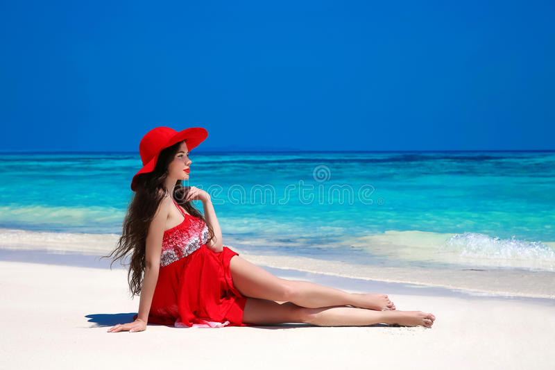 Happy beautiful woman in red hat enjoying sunny day lying on exotic beach in summer by tropical blue water. Attractive girl in re royalty free stock photos