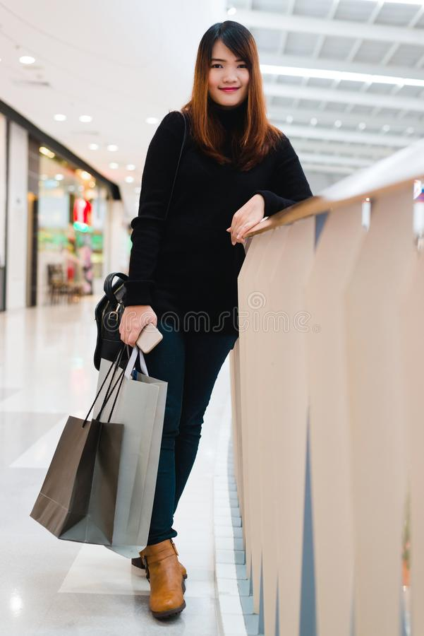 Happy beautiful woman with shopping bags stands at shop. Attractive asian woman with purchasing bags in big mall. stock images