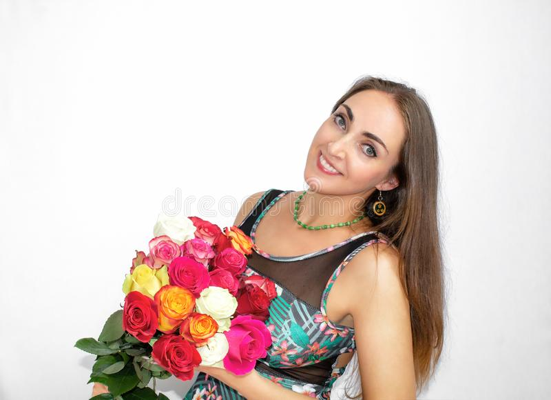 Happy, beautiful woman sitting with a bouquet of roses, on a black background. A gift for woman.A happy, beautiful woman is sittin stock photos