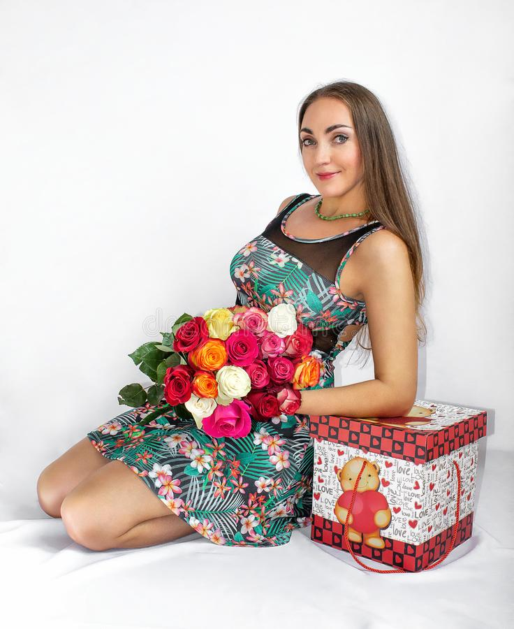 A happy, beautiful woman is sitting with a gift box and a bouquet of roses, on a white background. Valentine`s Day. royalty free stock photography