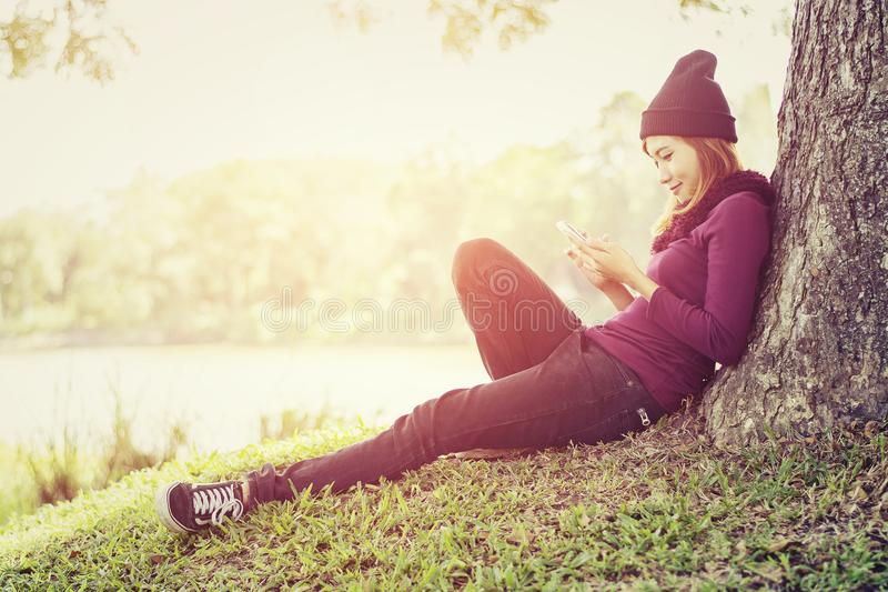happy beautiful woman sitting under the tree playing mobile phone in the park royalty free stock photo