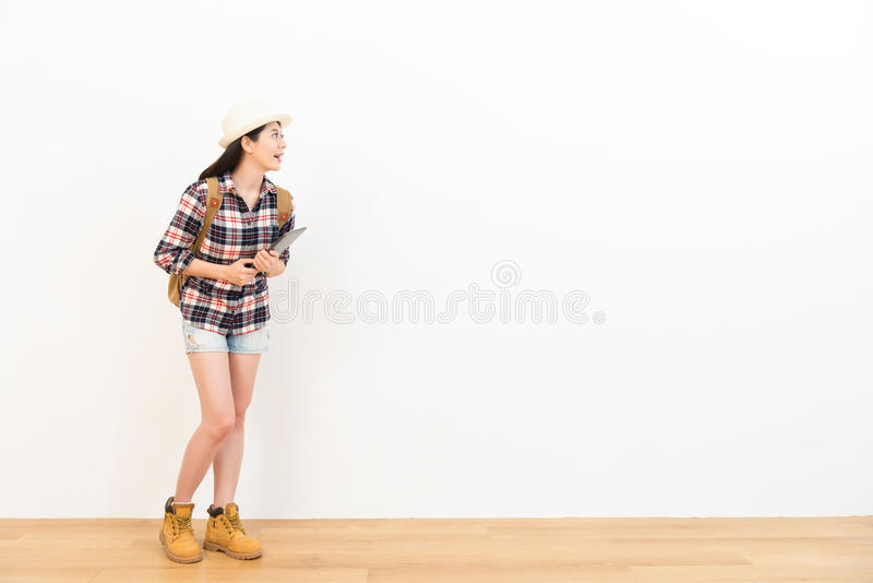 Happy beautiful woman standing on wooden floor. Looking at white background and holding the digital tablet computer guidebook thinking of travel plan royalty free stock photos