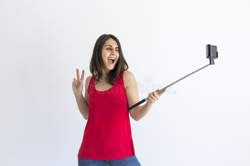 Happy beautiful woman taking a selfie with smart phone over white background. Lifestyle. Wearing casual clothing and smiling. stock photos