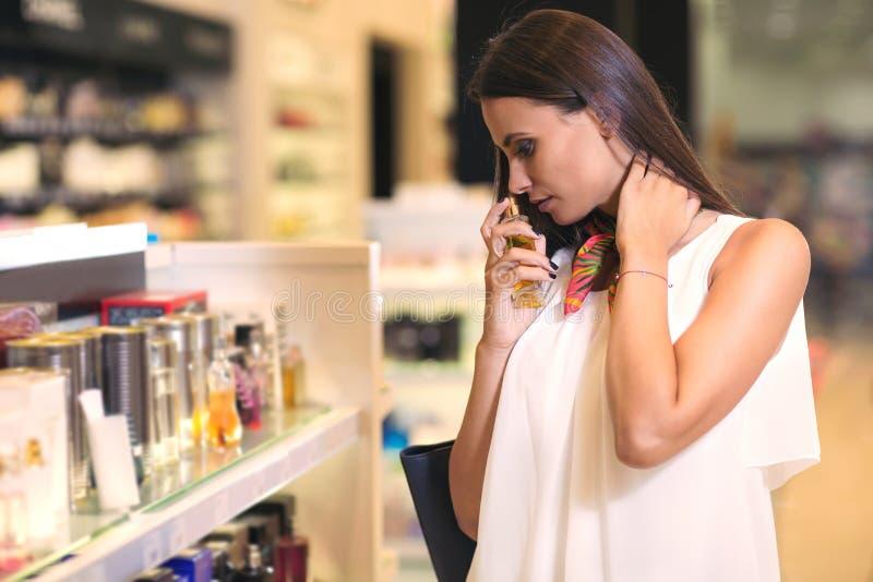 Happy beautiful woman testing perfumes stock photo