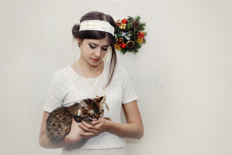 Happy beautiful woman in vintage dress holding cute kitten on wh royalty free stock photo