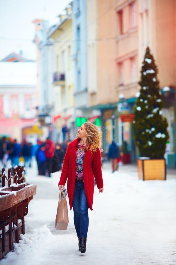 Happy beautiful woman walking on crowded street in winter royalty free stock image
