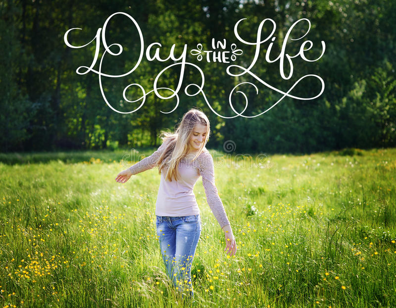 Happy beautiful woman walking on a spring meadow and text Day in the life. Calligraphy lettering vintage hand draw stock images