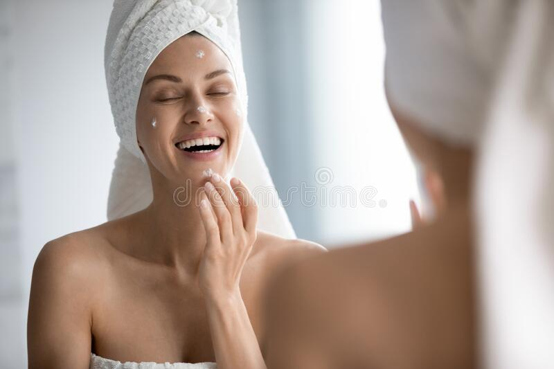 Happy beautiful woman applying cream on face in bathroom royalty free stock image