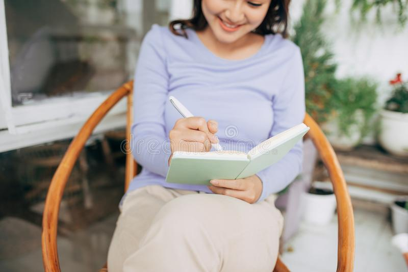 Happy Beautiful Woman writing something into her diary. Enjoying morning. Relaxed time stock photos