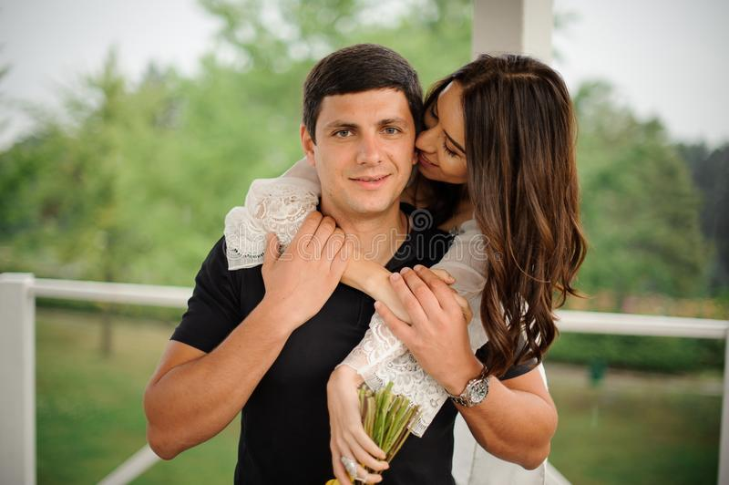 Happy and beautiful woman hugging her smiling boyfriend from back stock images
