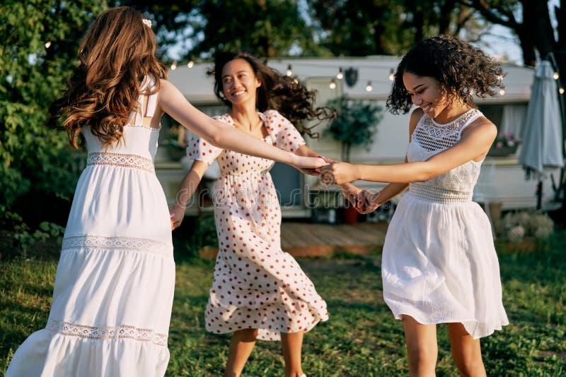 Happy beautiful women dancing in circle during a picnic. Multi ethnic girls having fun together outdoors. Caucasian, african american and asian girls enjoying stock images