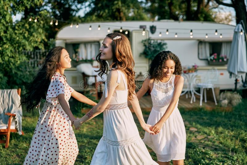 Happy beautiful women dancing in circle during a picnic stock photography