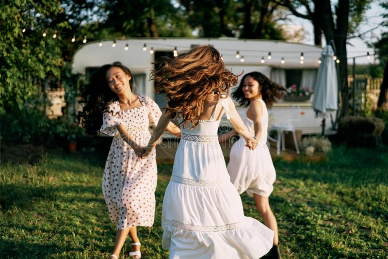 Happy beautiful women dancing outdoors on picnic royalty free stock photo
