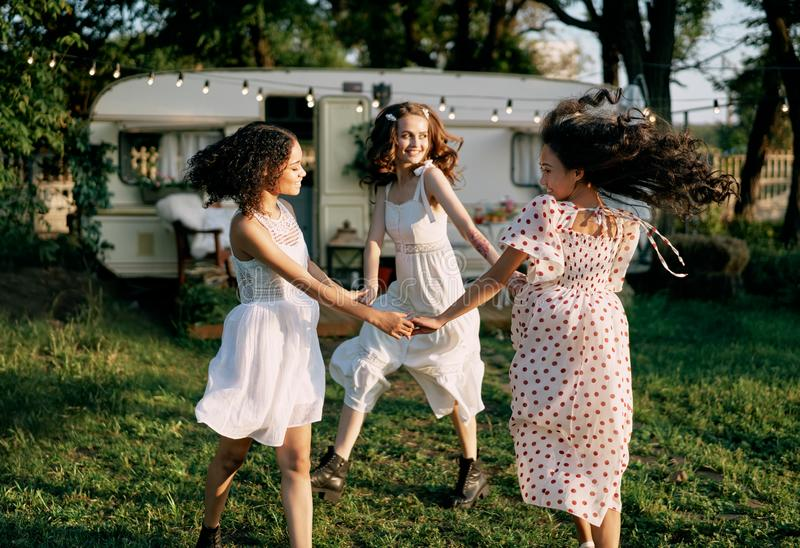 Happy beautiful women dancing outdoors on picnic royalty free stock image