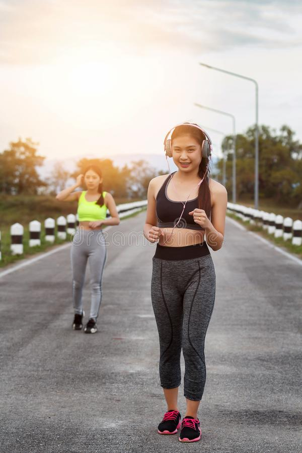 Happy and beautiful women joggers running on road. Fitness and workout wellness concept stock photography