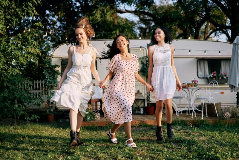 Happy beautiful women running and having fun together outdoors during a picnic royalty free stock image